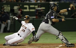 Yomiuri Giants Yoshinobu Takahashi slides into home plate past Seattle Mariners catcher Jesus Montero in the second inning during their exhibition game at Tokyo Dome