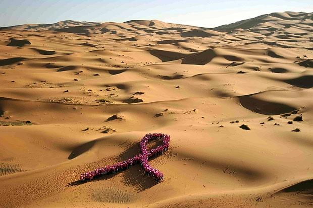 Dune tinte di rosa - Un fiocco rosa tra le dune: le concorrenti del Trofeo «La rosa del deserto» rendono omaggio in questo modo al partner della competizione, l'associazione francese per la lotta contro il cancro al seno «Cancer du sein, palons-en!» , nella regione di Merzouga, nel deserto del Marocco. Nello stato africano si sta svolgendo la dodicesima edizione della gara stile Parigi-Dakar, riservata alle donne (Afp/Julien Rocher)
