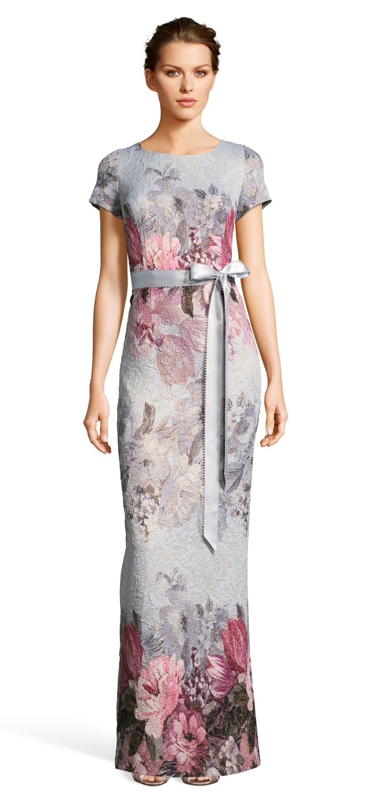 Beautiful blooms blossom throughout this beloved look. This formal dress features a circle neckline, short sleeves, a fitted bodice with a satin ribbon self-tie sash that nips at the waist, and a long column skirt with a slit at the back. Florals fade in and out of view throughout the printed jacquard fabric that has stretch. A zipper closure can be found at the back. We love this floral dress for any member of the bridal party from mom to bridesmaids.