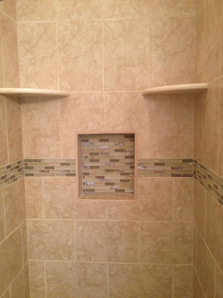 Beige tiled shower with two corner shelves and a niche filled with glass mosaics.