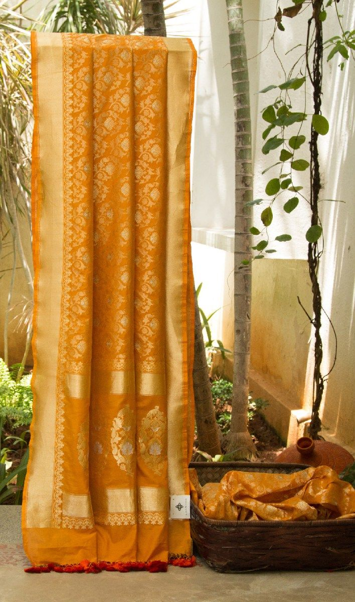 This rich honey-orange Benares Silk comes with exquisite floral zari work across the body, pallu and border. A complementingblouse in honey-orange with zari enhances the sari.