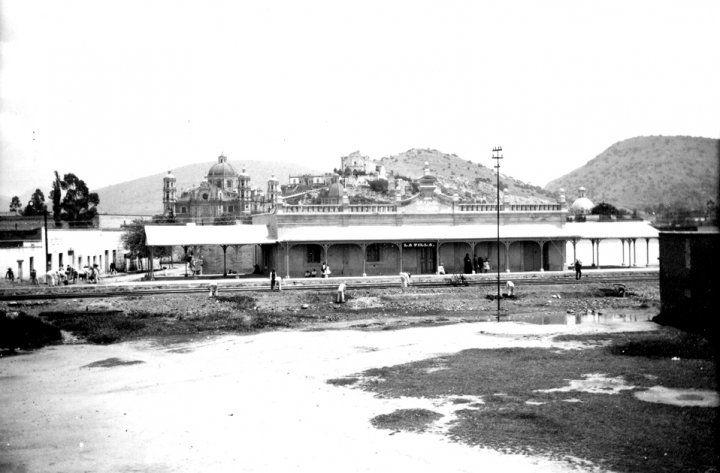 Estacion de trenes de la Villa de Guadalupe que data desde el 4 de julio de 1857,y a las 12 del día se inauguraró el tramo de Tlatelolco a la Villa de Guadalupe haciendo el recorrido por la Calzada de los Misterios. solo hasta 1878 se construye el edificio de la estación, subsistiendo hasta el servicio hasta el 28 de marzo de 1990. Actualmente el edificio aun existe y es sede del Museo de los Ferrocarrileros. Al fondo se observa el Cerro del Tepeyac con su antigua capilla y la Antigua…