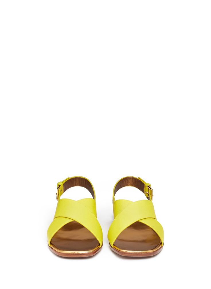 Celebrate summer in tangy tones with these lemon-hued sandals from Marni. Rendered in a simplistic cross-strap design with a textured leather, this pair simultaneously defines zesty vibrance and contemporary cool. Wear them to highlight solid palettes.