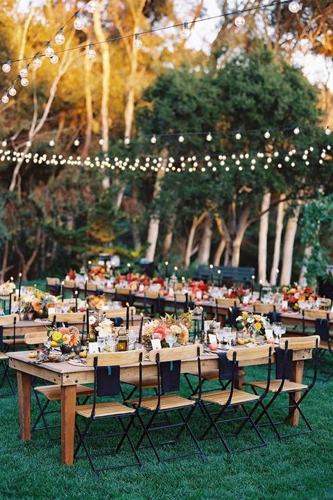 outdoor summer wedding with strung lights hanging above the reception tables