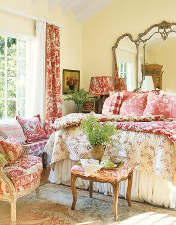 Cottage Bedroom:   To make this cozy cottage bedroom appear bigger than it actually is, a 19th-century French glass is used as a grand headboard. The combination of patterns — toiles, stripes, and florals — works because they are all shades of red, from pink to rose to deep burgundy.