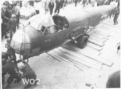 Strand van Scheveningen: Klandestien gemaakte foto's (door gat in jas) van door de RAF neergeschoten Luftwaffe-toestellen (Junker). Burgers kijken toe.   Beeld Datum Periode: zomer 1940