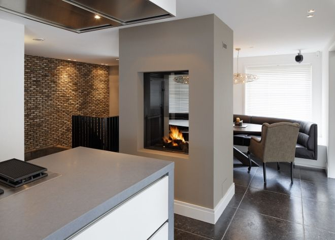 Doorkijkhaard in de keuken tussen eetkamer en kookgedeelte. Haard van Boley