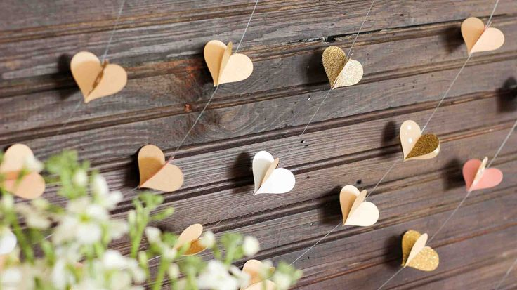 This handmade paper heart garland also adds beautiful texture and a hint of charm as a wedding photo booth backdrop. It makes a super sweet DIY Valentine's Day decor idea. Bonus: easy craft project to use up your scrapbooking paper scraps! Click to view full tutorial. | MakeAndDoCrew.com