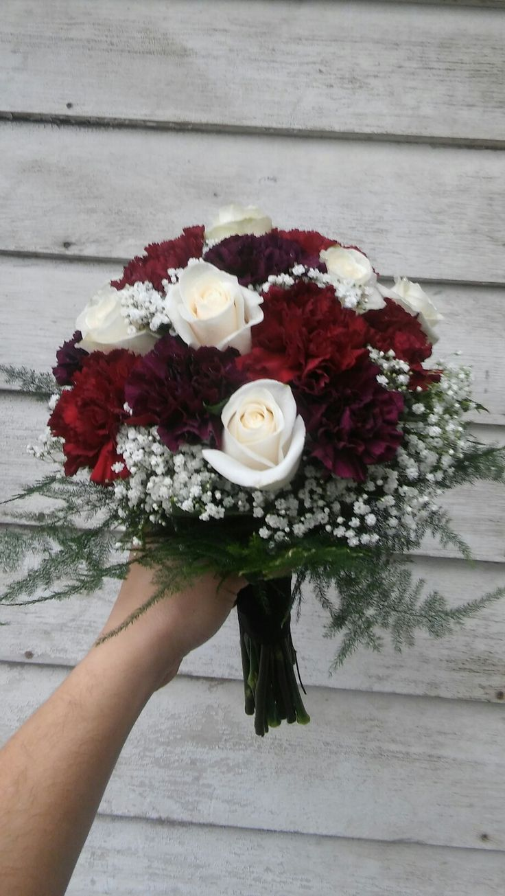 Rich colored bridal bouquet of burgundy and deep purple carnations, cream roses and baby's breath