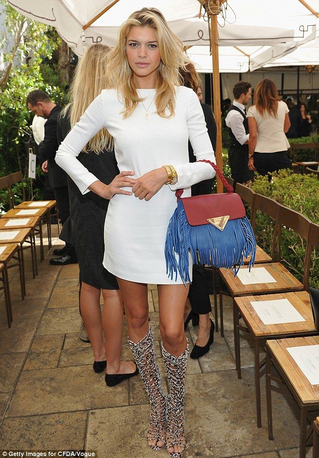 Leggy: Kelly Rohrbach - currently dating Leonardo DiCaprio - opted for a white mini dress and gladiator style boots
