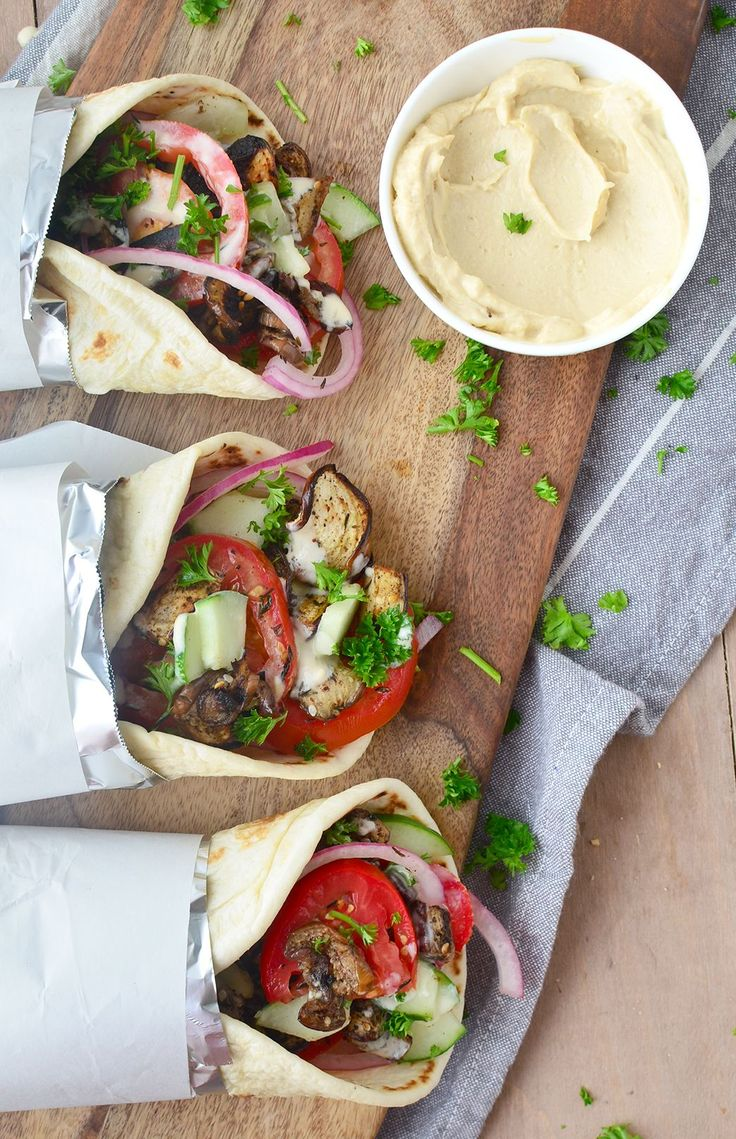 Vegan Eggplant Gyros! Za'atar seasoned eggplant stuffed into warm pita and topped with juicy tomatoes, crisp cucumbers, and the BEST hummus-dill sauce. You've gotta try these!