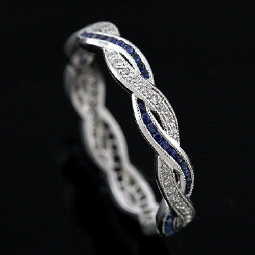 This beautiful vintage style replica infinity band contains round brilliant diamonds (Approx. .15Cttw) pave set and round blue sapphires (Approx. .23Cttw) set in channel. Diamonds are G-H color and VS