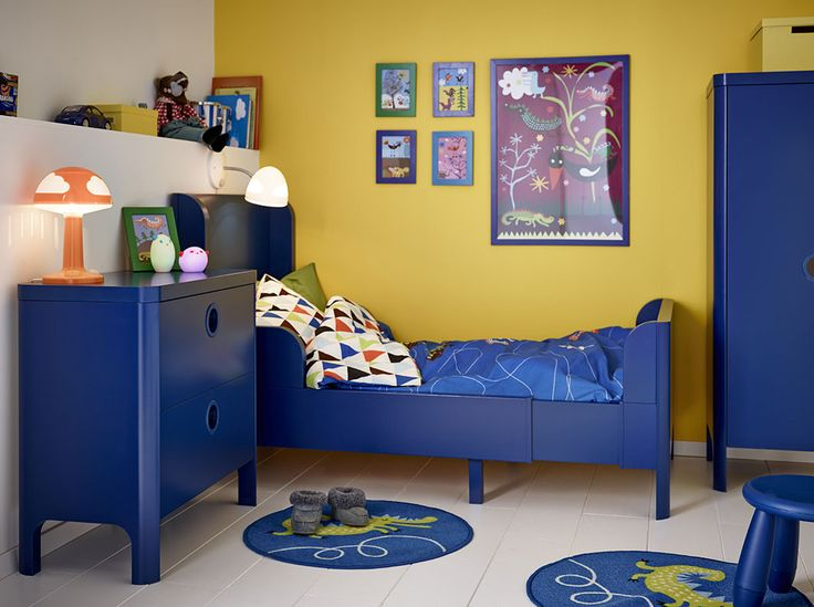 A children's room with a blue extendable bed with matching chest of drawers and wardrobe