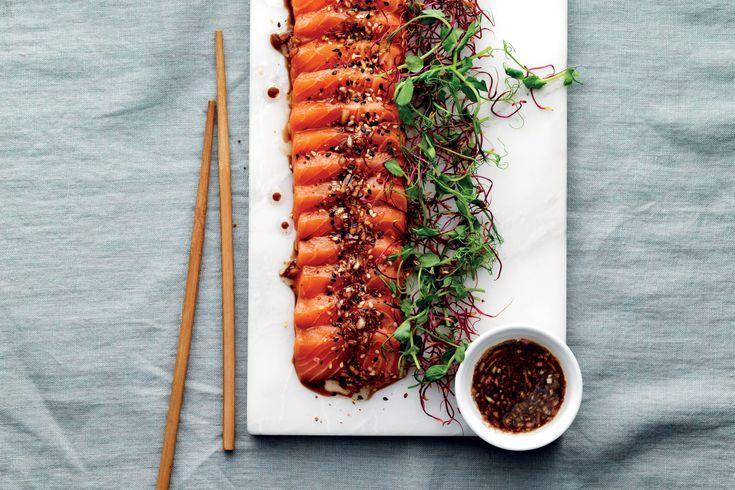 Laxsashimi är enkelt att göra hemma. Skär bitar av rå lax och toppa fisken med salladsskott, wasabi och sojadressing.