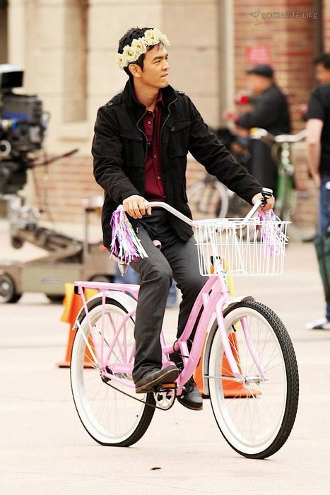 John Cho. With a flower crown. On a pink Schwinn Lakeshore stepthrough bike. My glee that this photo exists is incandescent.