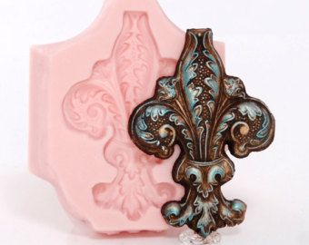 Silicone Mold Creates a Large Scroll Work Piece That Measures: 110mm x 65mm x 9mm thick or 4 & 13/16ths inch x 2 & 9/16ths inches x 3/8ths thick Please look at the second image for a visual of the size. Samples are not included. Detailed filigree scroll mold with fancy fish and shell design creates perfect pieces from fondant, gum paste, sugar for cake decorating. This piece would be great for scrapbook, card embellishments or jewelry. Your molded piece will pop right out of your mold ...