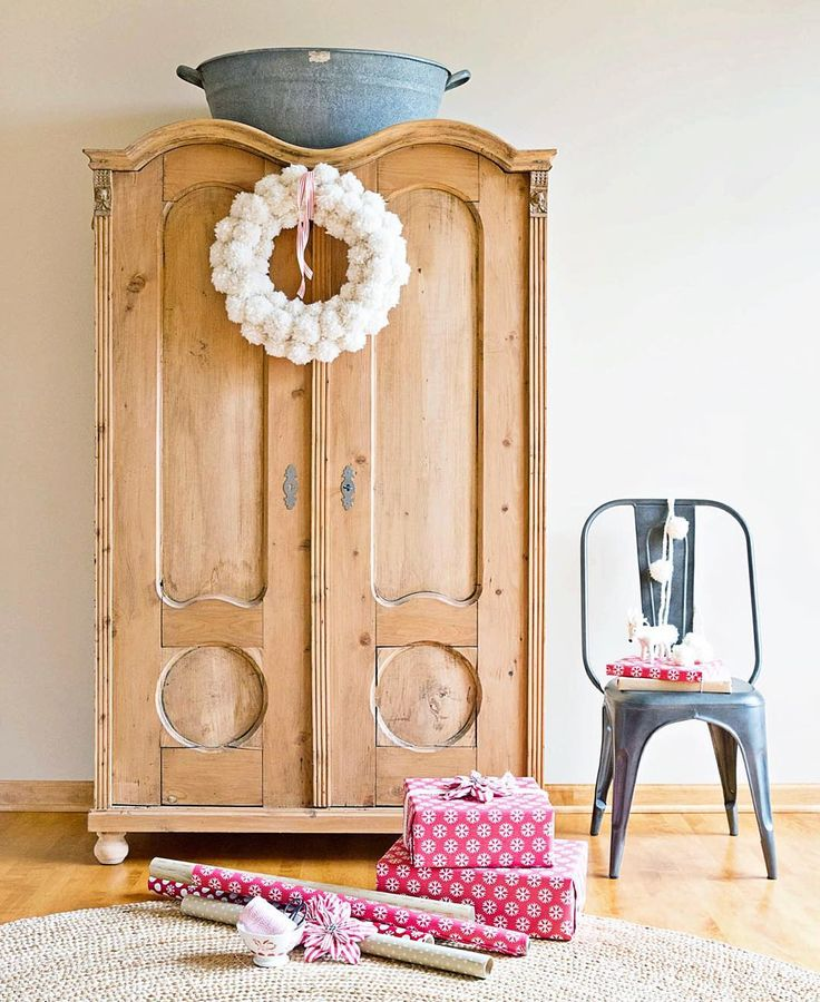 Farmhouse Christmas decor with a scrubbed wood armoire with arched doors, fluffy pom pom wreath, and gifts wrapped in pink - A Rosy Note.