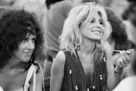 Emmy DE * ca. August 15-17, 1969, Near Bethel, New York, USA — Sally Mann (later the wife of Spencer Dryden), holding a joint, sits next to Grace Slick at the free Woodstock Music and Art Fair