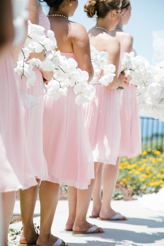 Love this for a beach wedding! Pink bridesmaid dresses + orchid bouquet and sandals. See more of This Girl Nicole Photography here. http://www.weddingchicks.com/vendor-guide/this-girl-nicole-photography/