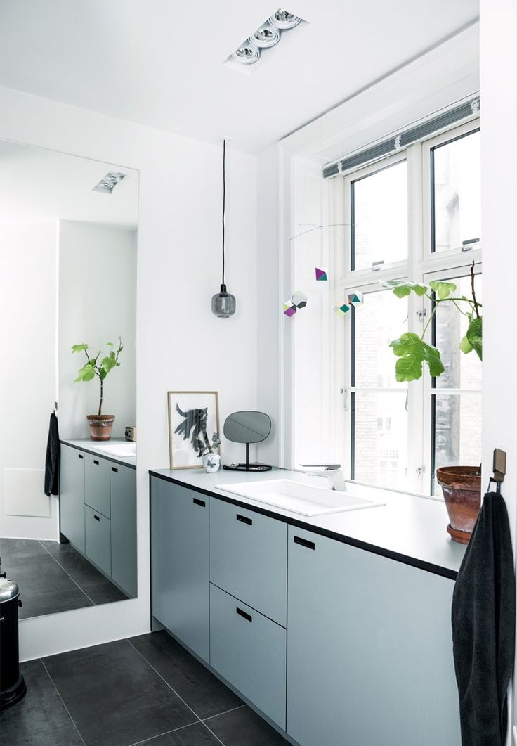Nordic and clean bathroom with light blue cabinets and integrated pulls/cut outs for handles