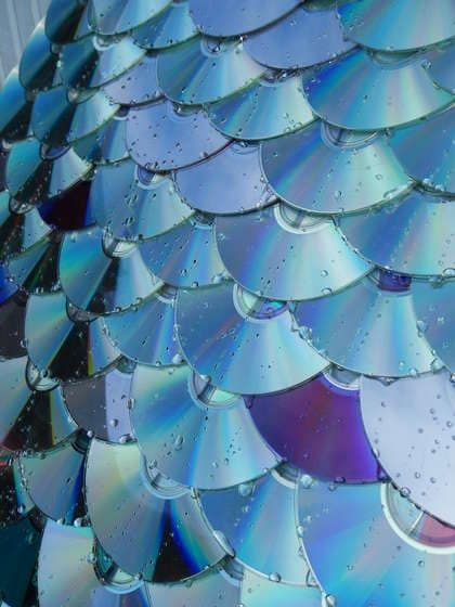 Roofing for sheds or dog houses made from upcycled CDs and DVDs. Simply drill a hole in each one, align, then nail to the roof.