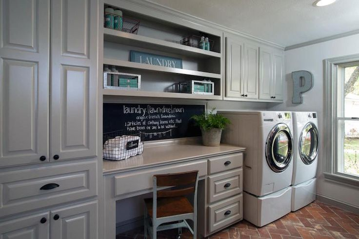 Fixer Upper - Country laundry room boasts gray raised panel cabinets adorned with oil-rubbed bronze knobs next to gray built-in desk paired with a chalkboard backsplash under built-in shelves beside white front-load washer and dryer atop brick pavers.