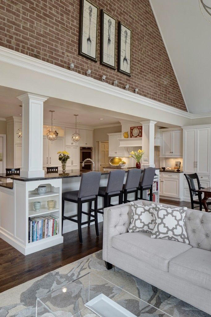 The kitchen expands into the open family room space, emerging beneath an immense vaulted ceiling with a red brick upper dividing wall. Rich dark hardwood flooring contrasts with light grey tones on the button tufted sofa, area rug, and bar stools. All-glass cubic coffee table sits in foreground, with built-in island shelving in white behind. <3