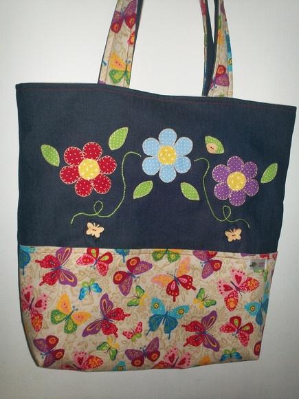Bolsa em patchwork, jeans e tecido 100% algodão, revestida com manta acrílica, forro, bolso interno e bolso externo com aplicações de flores feitas a mão. Fino acabamento. Fechamento em botão de ímã, medindo 40x 40 cm. R$60,00
