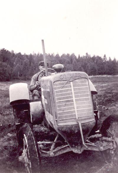 Taavetti Laatanaho ajaa traktoria 1930-luvulla. Riistaveden ensimmäinen traktori oli Melalahdessa Laatanaholla 1920-luvulla ja leikkuupuimuri 1950-luvun alussa.