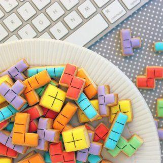 Bunte Keks Ausstecher in Form von Tetris Bausteinen, bunt glassiert auf Teller neben Tastatur