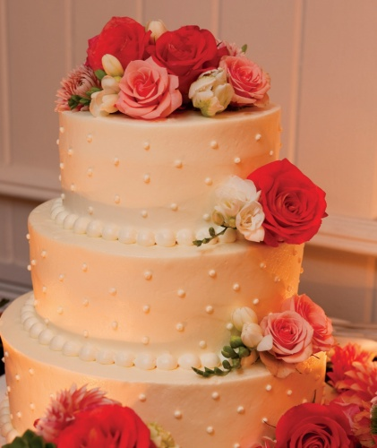 Wedding cake - butter cream frosting, polka dots, decorated with pink roses - Check out navarragardens.com for info on a beautiful Oregon wedding destination!