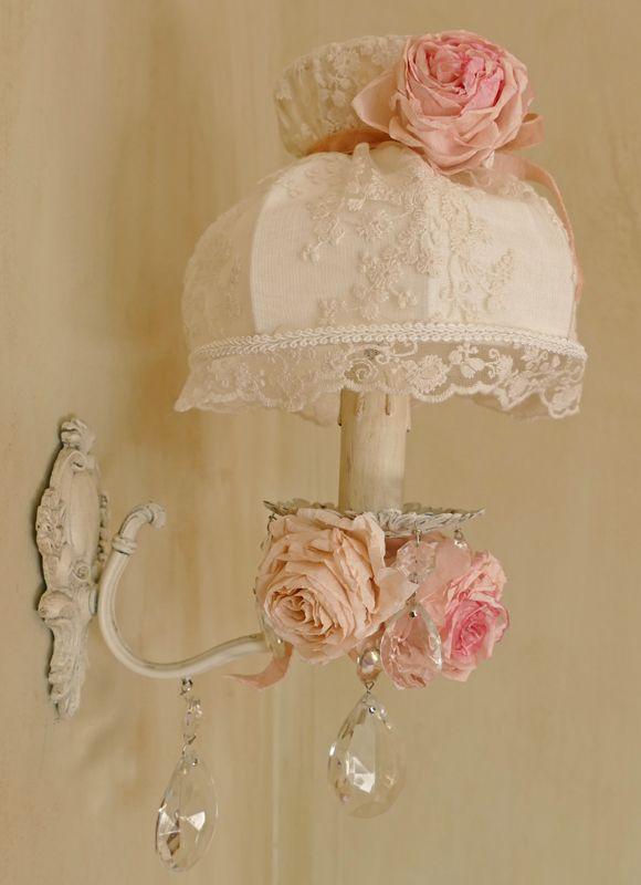 Applique simple peinte en ivoire et légèrement patinée d'une teinte grise, ornée de pampilles en cristal et de roses en papier. Abat-jour dôme à col diamètre 15 cm, tendu de dentelle ivoire et doublé, ceint d'un bouquet de roses . http://www.perledelumieres.com/#!product/prd1/3582124381/aplique-simple-aux-roses-et-son-abat-jour