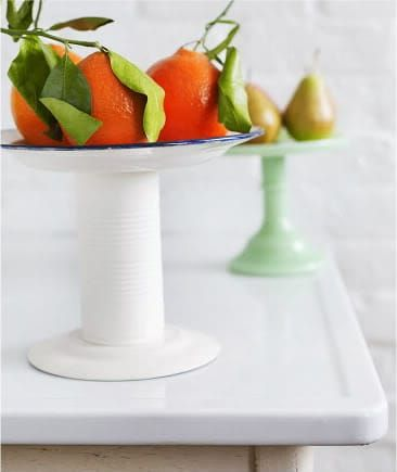Paint a tin can to match your plate, then use strong glue to attach the can to the bottom of the plate.