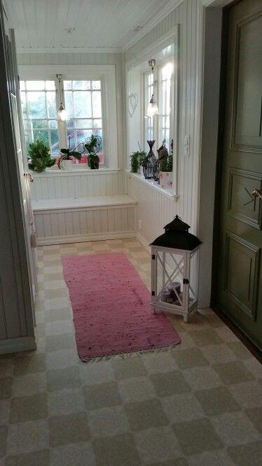 Hall med platsbyggd sittbänk/förvaring. Garderob gjord av gamla pardörrar. Pärlspont i ljusgrå nyans på väggarna.