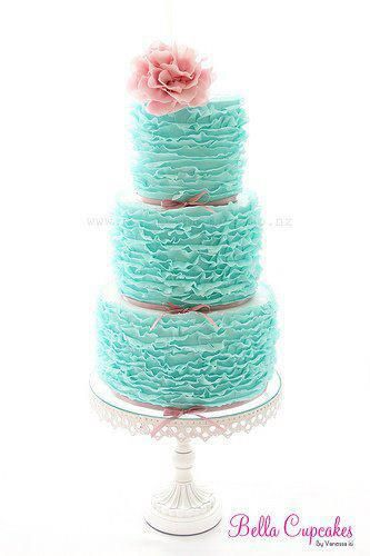 The top tier of this cake surround by tiers filled with individual cup cakes.... this it the color aqua/teal/blue!!