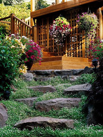 A unique pathway -- made from large boulders nestled into the ground -- connects the backyard gardens to the patio