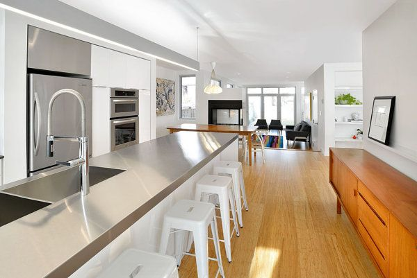 Wooden accents in a white kitchen with stainless steel cabinets