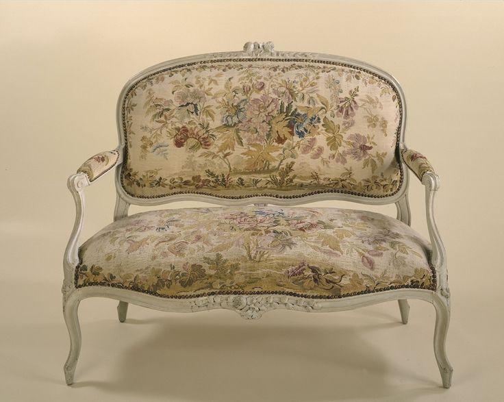 Ce canapé fait partie d'un ensemble « à la Reine », c'est-à-dire à dossier droit, destiné à être placé contre un mur ou une boiserie, contrairement aux sièges à dossier incurvé ou « en cabriolet » que l'on disposait à son gré dans la pièce. Ce siège relève d'un style Louis XV classique : dossiers plats dont la partie supérieure forme une courbe régulière, pieds cambrés en S, attache des consoles d'accotoir en volutes nervurées à l'aplomb des pieds, ornementation sculpt...