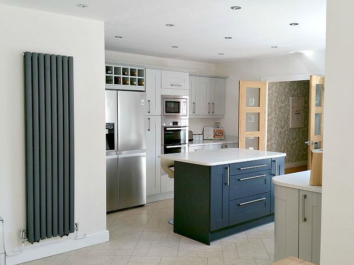 light grey shaker kitchen cabinets with charcoal island and modern tall vertical grey radiator, integrated wine rack
