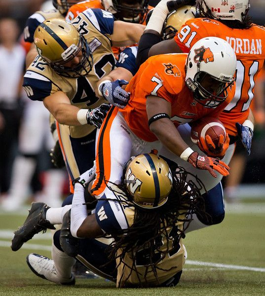 B.C. Lions' Tim Brown, right, is tackled by Winnipeg Blue Bombers' Rene Stephan, left, and Alex Suber during the first half of a CFL football game in Vancouver, British Columbia on Monday Aug. 5, 2013. (AP Photo/The Canadian Press, Darryl Dyck)