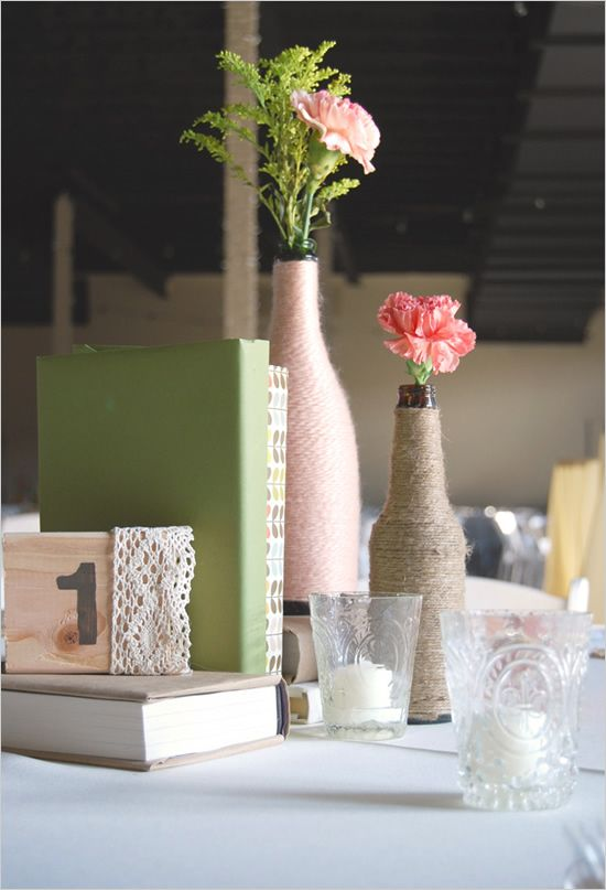 hand painted blocks used for table numbers with yarn wrapped bottles and a single flower