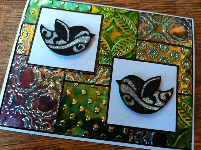 Shimmer Sheetz patchwork back ground! This is such a great technique! I started with silver metallic, used alcohol inks, embossed and rubbed over the embossed parts with the StazOn inkpads. For the birds I used the bird die, black velvet adhesive sheets and the tape on white card stock with the 625 Sky Silk Microfine glitter.