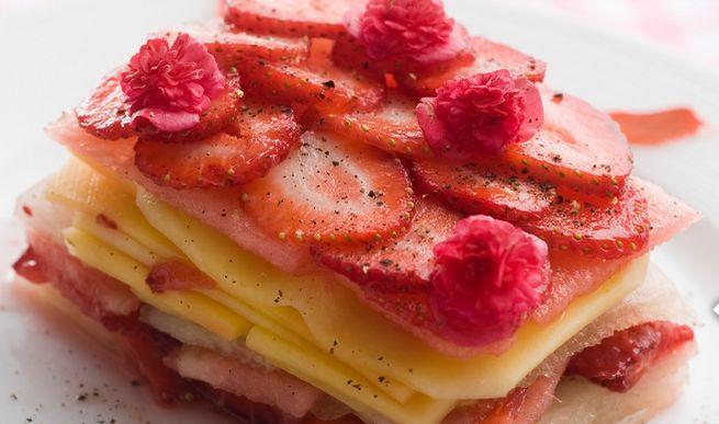 Fruitlasagne; 2 mango's 250 g aardbeien 2 citroenen 2 el honing eetbare bloemen;  Schil de mango's en snij het vruchtvlees in dunne plakken. Gebruik een klein mes om het vruchtvlees van de pit te schrapen en leg het vervolgens aan de kant.  Snij de meloen en watermeloen in dunne reepjes. Snij de aardbeien in plakken. Doe het sap van 2 citroenen, het overgebleven mangovlees en honing in een kom en roer goed. Leg een folievel in een schaal op op een bord. Maak de 'lasagne' bovenop de folie.