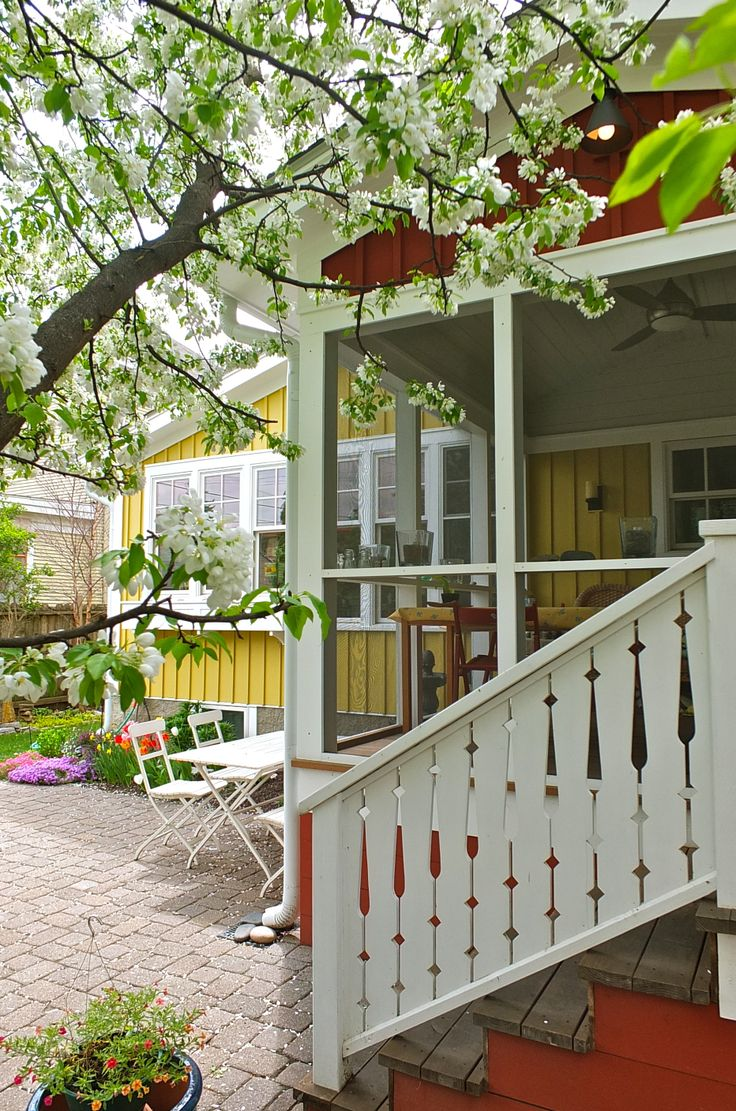 "Exterior view of porch, with Swedish decorative railing detail, and kitchen in background, both with traditional vertical board and batten siding (8"" on center). Our color inspirations were drawn from traditional Swedish exterior colors, ""herrgårdsgul"" or Swedish manor house yellow, and ""faluröd"" or Falun red. The off-the-shelf paints we used to approximate those colors were Behr's Egyptian Temple and Sherwin Williams Roycroft Copper Red."