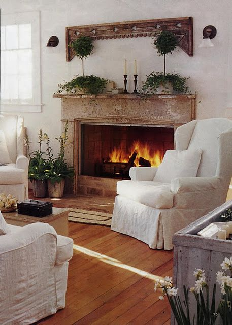 Keep the home fires burning...beautiful rustic sitting room fireplace with pretty mantle display framed by two cosy antique white slipcovered armchairs to read or doze in on a cold winter evening...
