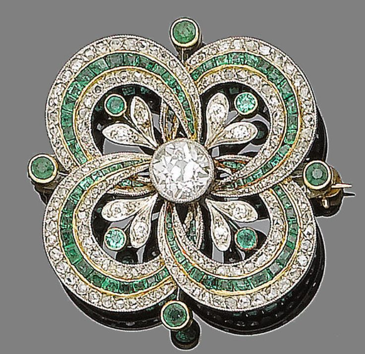 Circa 1915 emerald and diamond brooch/pendant, centrally-set with an old brilliant-cut diamond within an openwork quatrefoil set with alternating rows of calibré-cut emeralds and rose-cut diamonds, accented with circular-cut emerald and single-cut diamond flowers, principal diamond approx. 0.85ct.