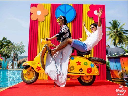 photo op with a colourful yellow scooter with flowers | Indian wedding photoshoot ideas | Indian wedding photo booth ideas | The wedding Salad | The ultimate guide for the Indian Bride to plan her dream wedding. Witty Vows shares things no one tells brides, covers real weddings, ideas, inspirations, design trends and the right vendors, candid photographers etc.| #bridsmaids #inspiration #IndianWedding | Curated by #WittyVows - Things no one tells Brides | www.wittyvows.com
