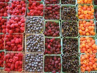When you get your berries home, prepare a mixture of one part vinegar (white or apple cider) and ten parts water. Dump the berries into the mixture and swirl around. Drain, rinse if you want (though the mixture is so diluted you can't taste the vinegar,) and pop in the fridge. The vinegar kills any mold spores and other bacteria on the surface. Raspberries will last a week or more, and strawberries go almost two weeks without getting moldy and soft.