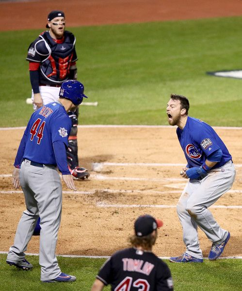 Ben Zobrist #18 of the Chicago Cubs celebrates with teammate Anthony Rizzo #44 after crashing into Roberto Perez #55 of the Cleveland Indians to score a run in the first inning on a double hit by Addison Russell #27 (not pictured) in Game Six of the 2016 World Series at Progressive Field on November 1, 2016 in Cleveland, Ohio.