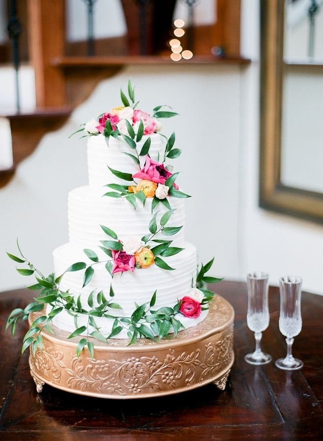 olive branch and ranunculus wrapped three tier wedding cake: http://www.stylemepretty.com/louisiana-weddings/new-orleans/2016/10/03/modern-colorful-new-orleans-destination-wedding/ Photography: Julie Paisley - http://juliepaisley.com/